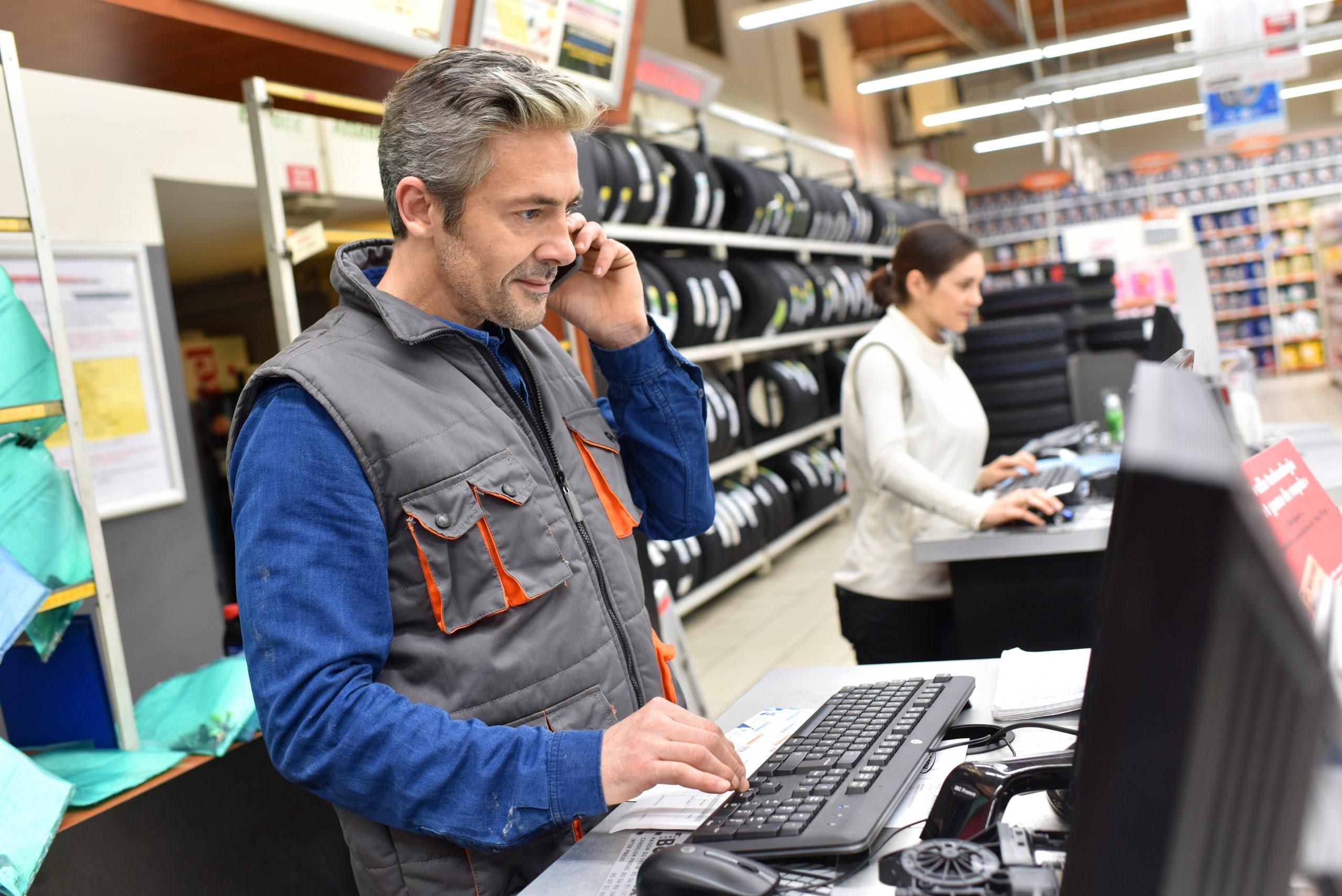 Vendeur da s un rayon pneumatique au téléphone avec un client