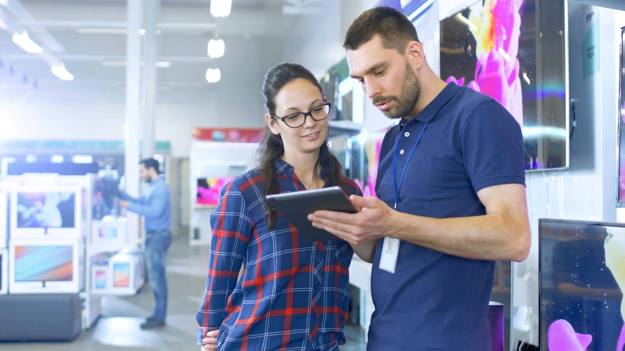 Vendeur dans un magasin avec sa tablette et une cliente